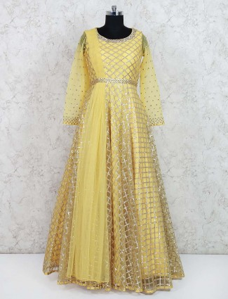 Yellow colored party wear net fabric gown
