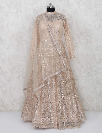 Embellished beige colored floor length suit in net fabric