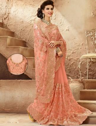 Wonderful peach net wedding wear designer saree